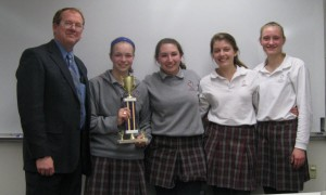 The Villa Duchesne teams (Rachel Arnold and Mary Hogan with trophy, Meghan Grojean and Nicole Saville providing team spirit) celebrate their winning titrations. Battle Coordinator Bruce Ritts presented the trophy.