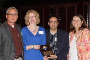Joyce Brown (in blue) receives the Outstanding High School Chemistry Teacher Award from Ziad Ramadan and Sandi Mueller while her spouse beams