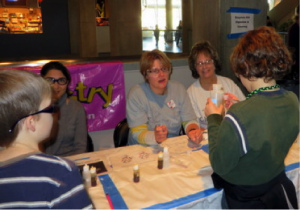 Pegah Jalili, Ann Feil, and Sheryl Loux explain about Enzymes Aid Digestion & Cleaning at the St. Louis Science Center for National Chemistry Week on 8/26/13.